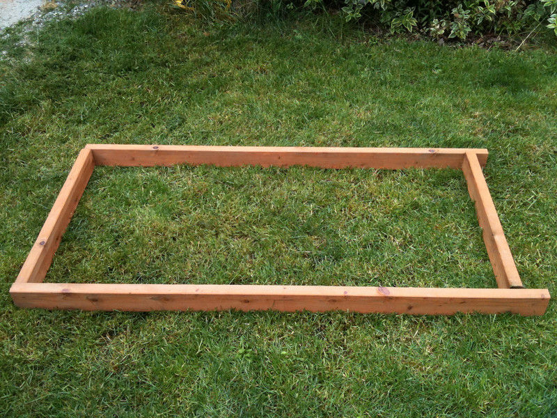 """First, lay out the pressure treated 2x4 lumber. Note that at the back, the long pieces extend beyond the cross-beam at the back by about 4 inches. The dimensions can be to your liking, but are approximately 30"""" x 60""""."""