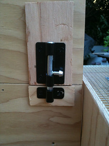 Install a latch on the nesting box wall door to keep it from swinging freely.