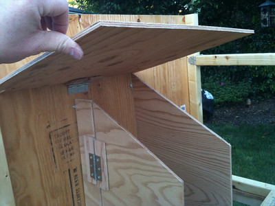Cut a suitable piece of plywood to form a roof over the nesting boxes, and attach it to the back wall with a hinge.