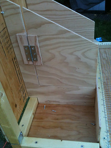 "Cut a door in the nesting box wall nearest to the side of the coop. This will allow you to access the inner nesting box. The door should be 3-4"" above the floor to allow ample room for nesting material which you'll install later. Then install the nesting box walls by screwing them to the 2x2 dividers already mounted on the floor."