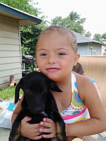 My daughter Yasmine rockin' her extra chromosome with her puppy (and best friend) Tico.<br /> <br /> Photographer's Name: Amanda Hernandez<br /> Photographer's City and State: Anderson, Ind.
