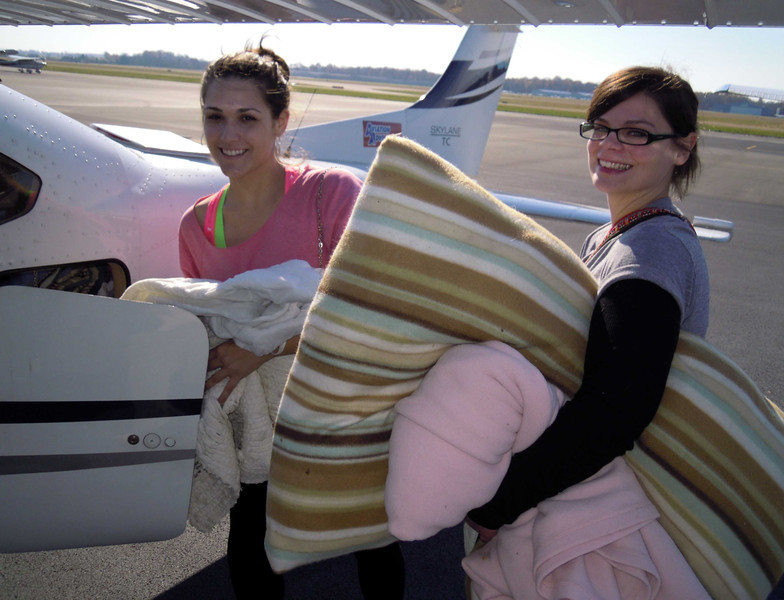 Elyse and Meg Help load the blankets and stuff into the plane at Manasses,VA.