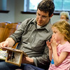 Russ and Adele Williston, 6, read a book about Wendlecat during an open house with TheraPAWS at Thayer Memorial Library in Lancaster on Wednesday evening to teach interested residents about how their pet can become a therapy pet. SENTINEL & ENTERPRISE / Ashley Green