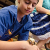Christopher Cragin Warner hangs out with a hermit crab during an open house with TheraPAWS at Thayer Memorial Library in Lancaster on Wednesday evening to teach interested residents about how their pet can become a therapy pet. SENTINEL & ENTERPRISE / Ashley Green
