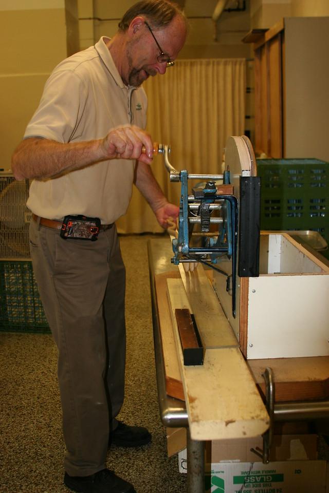 #9   paul scott cranking the handle on the extruding machine