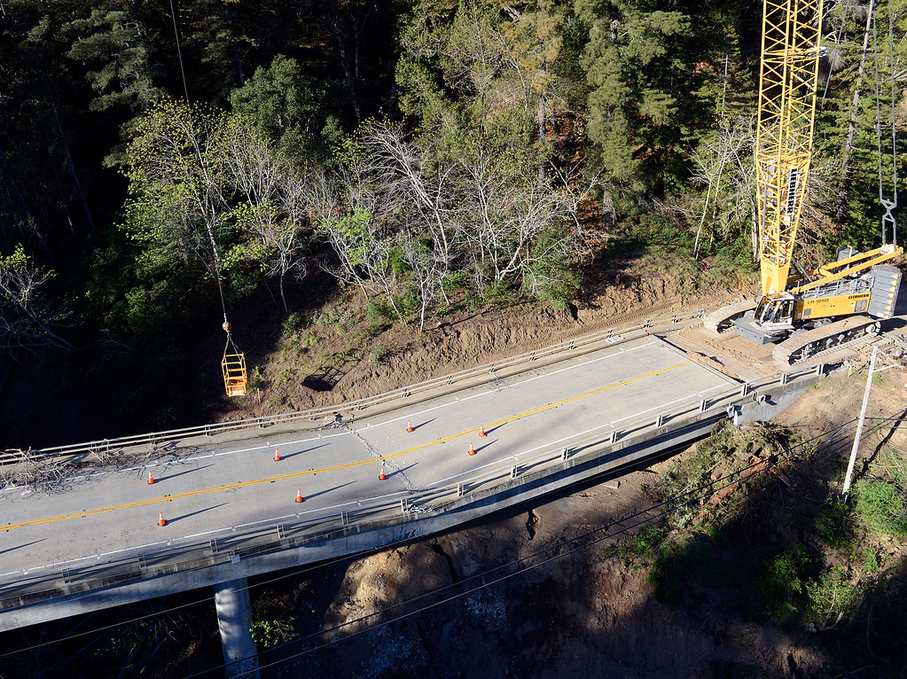 . A crane operator moves a box over a fracture on the Pfeiffer Canyon Bridge in the early morning before adding wrecking ball to dismantle the structure on Highway 1 in Big Sur, Calif. on Monday March 13, 2017. The bridge was compromised after slides occurred in the area associated with this winter\'s heavy rains.  (David Royal - Monterey Herald)
