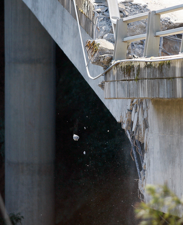 . Cement chips fall from the storm damaged Pfeiffer Canyon Bridge in Big Sur as crews use a 6,000 pind wrecking ball attached to a crane on Thursday, March 16, 2017.  (Vern Fisher - Monterey Herald)