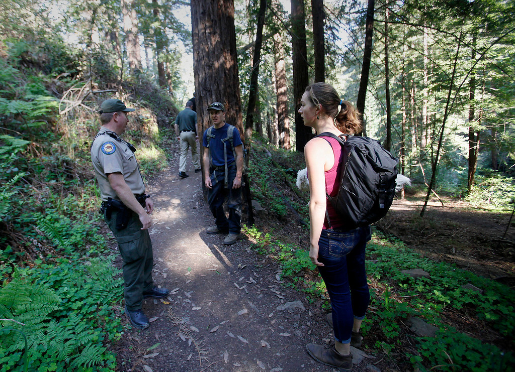. California State Park ranger Brian Powell talks with David and Haley Seefeldt as the walk south on the new Pfeiffer Canyon trail foot that is open to residents traveling around the former Pfeiffer Canyon bridge and Pfeiffer Big Sur State Park on Thursday, March 30, 2017.  (Vern Fisher - Monterey Herald)