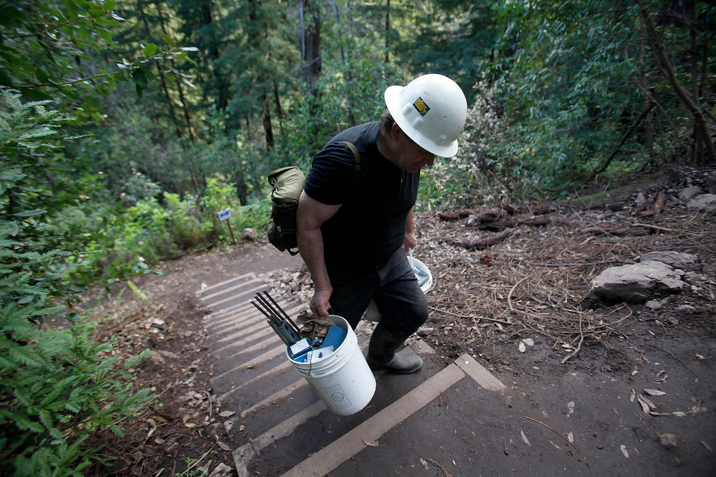 . Contractor Tom Massaglia hauls construction equipment up the new Pfeiffer Canyon foot trail that is open to residents traveling around the former Pfeiffer Canyon bridge and Pfeiffer Big Sur State Park on Thursday, March 30, 2017.  (Vern Fisher - Monterey Herald)