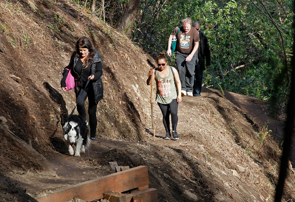 . People walk south on the new Pfeiffer Canyon foot trail that is open to residents traveling around the former Pfeiffer Canyon bridge and Pfeiffer Big Sur State Park on Thursday, March 30, 2017.  State Park officials have asked residents not to bring their dogs or pets while using the trail.  (Vern Fisher - Monterey Herald)