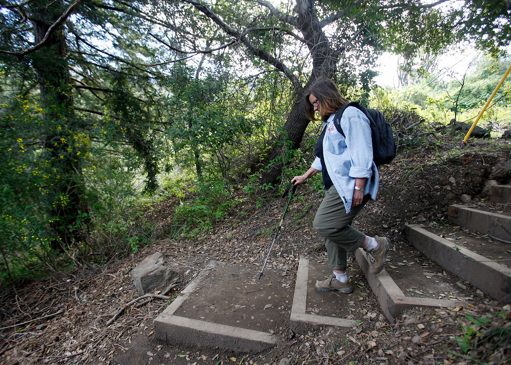 . Big Sur resident Nadine Clark walks north on the new Pfeiffer Canyon foot trail traveling around the former Pfeiffer Canyon bridge and Pfeiffer Big Sur State Park on Thursday, March 30, 2017.  (Vern Fisher - Monterey Herald)