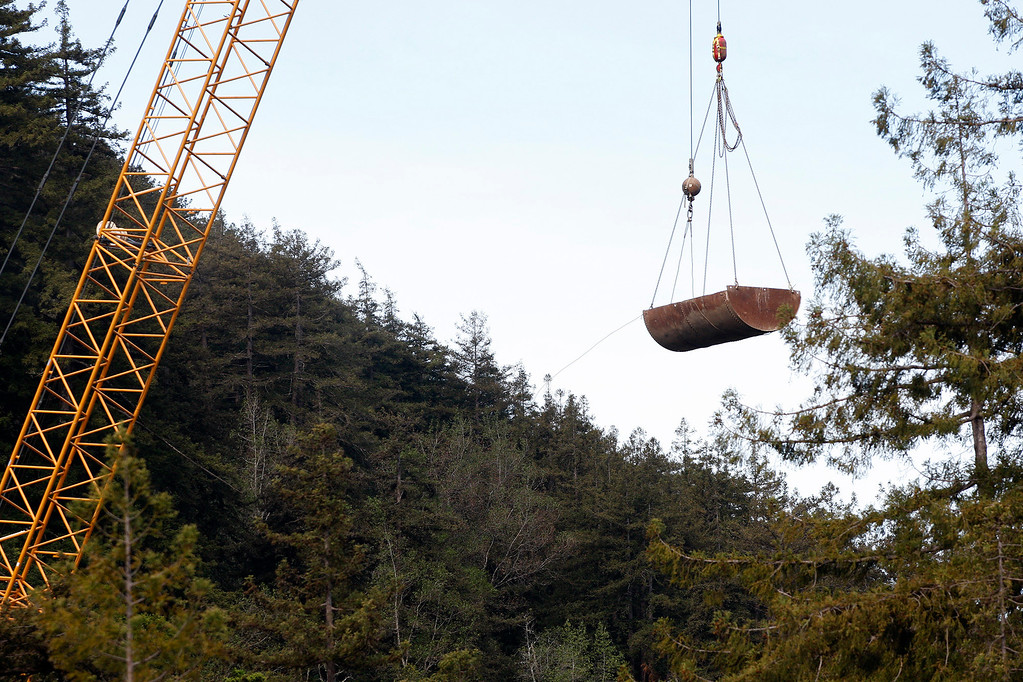 . A large crane removes concrete debris from the bottom of Pfeiffer Canyon as work continues at the Pfeiffer Canyon bridge construction area on Highway One on Thursday, March 30, 2017.  (Vern Fisher - Monterey Herald)