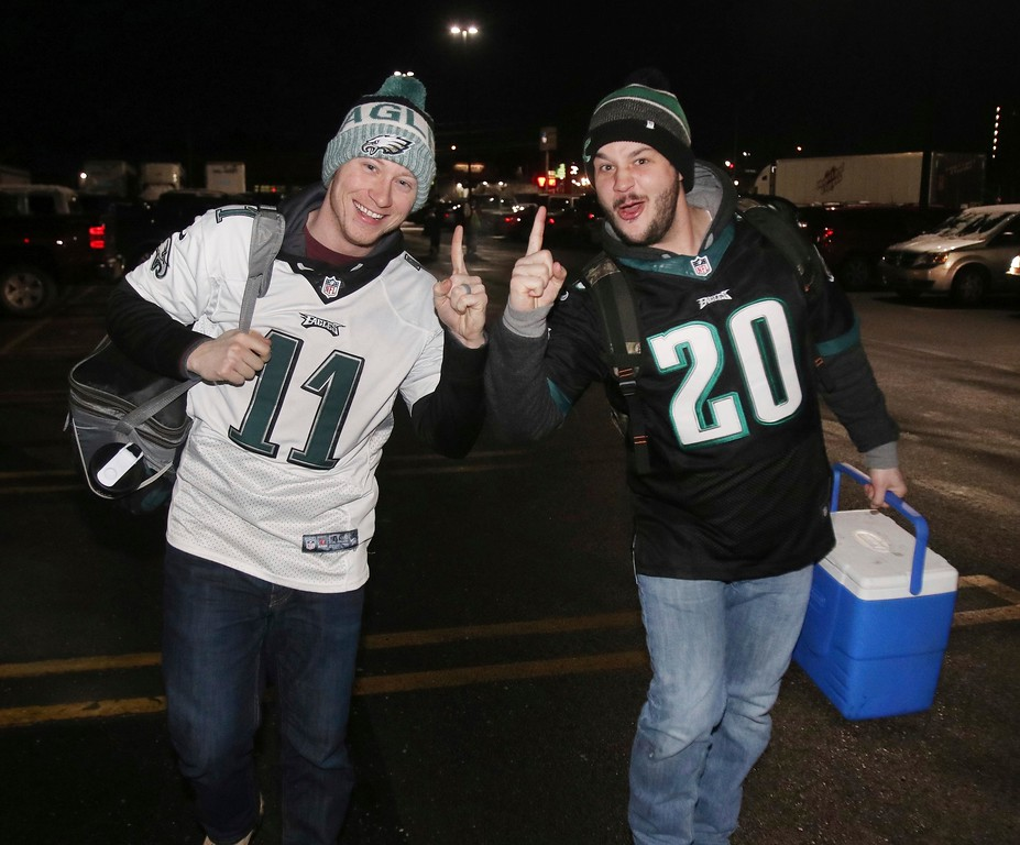 . Philadelphia Eagles NFL football team fans Corey Klinger, left, and Greg Mullins are all smiles as they head to their bus to Philadelphia for the Super Bowl champions parade, in Wilkes Barre Township, Pa., early Thursday, Feb. 8, 2018. (Dave Scherbenco/The Citizens\' Voice via AP)