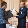 A member of DC Mayor Muriel Bowser cabinet gives a greetings declaration to Jean-Michel Giraud,  President & CEO of Friendship Place,  on behalf of the Mayor