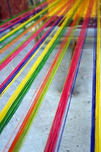 Weaving threads at the BeeFarm, Bohol by Nancy Loehrke.