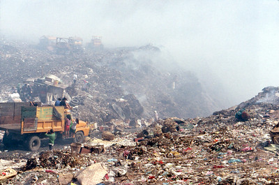 A constant flow of dump trucks brings new garbage along well developed roads.