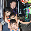 Mira S Bulloc and her children in the front room of their house where she sells clothing.