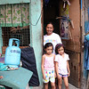 Malon R Pepito and her two daughters out side their home with a propane tank. They own 30 tanks and exchange them our for their clients.