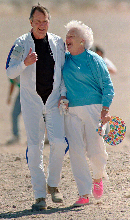 ". FILE - In this March 25, 1997, file photo, former President George H.W. Bush gets a hug from his wife Barbara after he made a successful parachute jump at the U.S. Army\'s Yuma Proving Ground outside of Yuma, Ariz. Former first couple George and Barbara Bush\'s relationship is a true love story, described by granddaughter Jenna Bush Hager as ""remarkable.\"" They met at a Christmas dance. She was 17. He was 18. Two years later they were married. Now 73 years later, with Barbara Bush declining further medical care for health problems, they are the longest-married couple in presidential history. (AP Photo/Mike Nelson, Pool, File)"