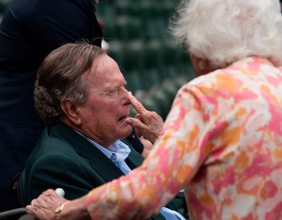 ". FILE - In this May 3, 2015, file photo, Barbara Bush applies sunscreen to the nose of her husband, former President George H.W. Bush, before the Seattle Mariners take on the Houston Astros in a baseball game in Houston, Texas. Former first couple George and Barbara Bush\'s relationship is a true love story, described by granddaughter Jenna Bush Hager as ""remarkable.\"" They met at a Christmas dance. She was 17. He was 18. Two years later they were married. Now 73 years later, with Barbara Bush declining further medical care for health problems, they are the longest-married couple in presidential history. (AP Photo/George Bridges, File)"