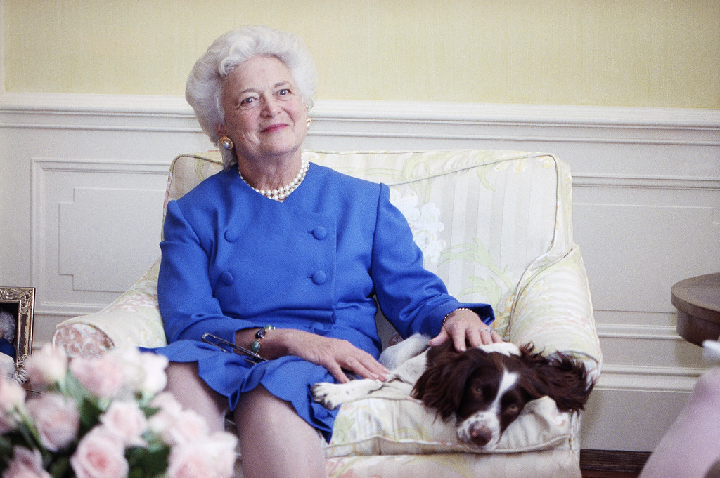 . FILE - In this 1990 file photo, first lady Barbara Bush poses with her dog Millie in Washington. A family spokesman said Tuesday, April 17, 2018, that former first lady Barbara Bush has died at the age of 92. (AP Photo/Doug Mills, File)