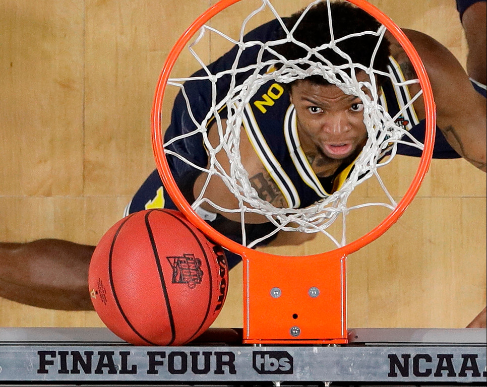 . Michigan\'s Zavier Simpson looks as the ball gets stuck between the basket and the backboard during the first half in the championship game of the Final Four NCAA college basketball tournament against Villanova, Monday, April 2, 2018, in San Antonio. (AP Photo/David J. Phillip)