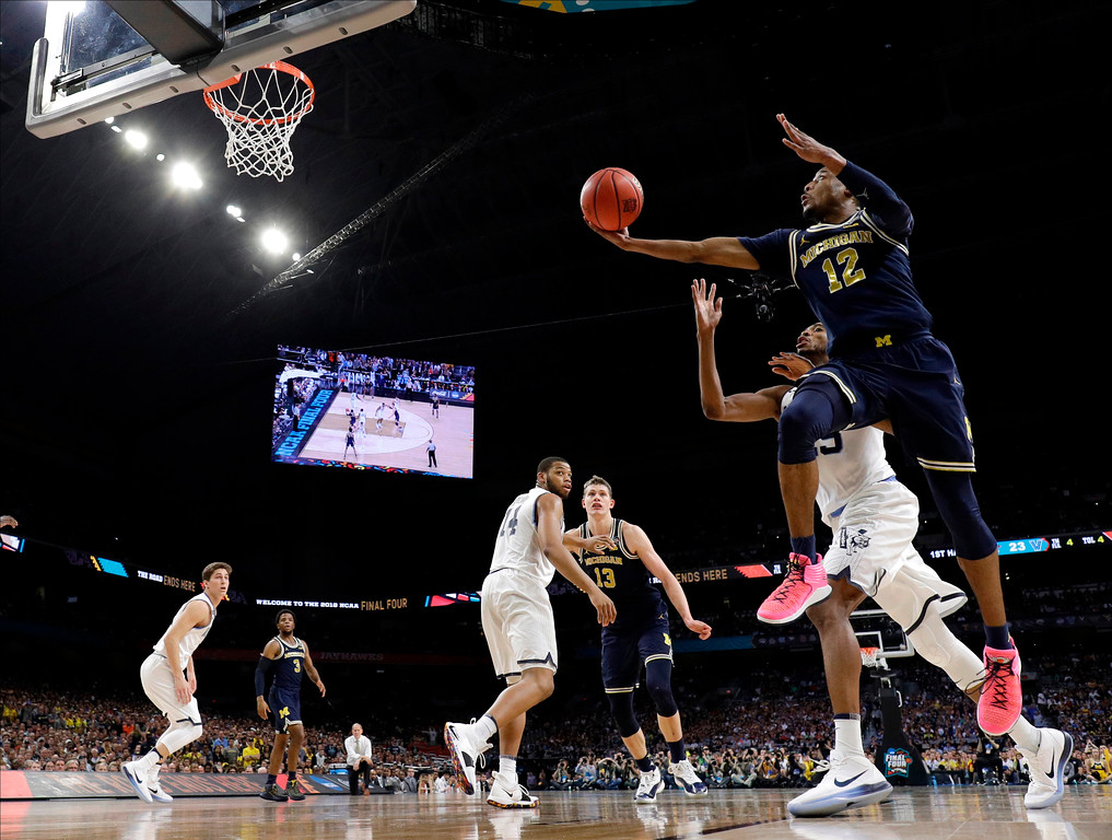 . Michigan guard Muhammad-Ali Abdur-Rahkman (12) drives to the basket over Villanova forward Jermaine Samuels during the first half in the championship game of the Final Four NCAA college basketball tournament, Monday, April 2, 2018, in San Antonio. (AP Photo/David J. Phillip)