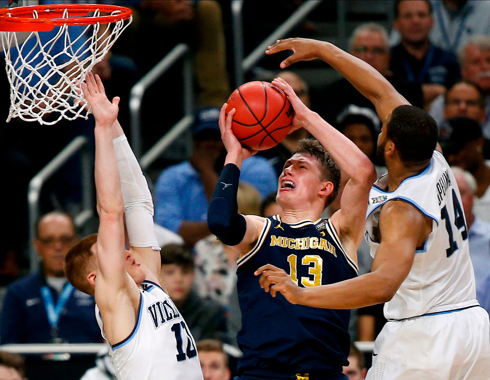. Michigan forward Moritz Wagner, center, drives to the basket between Villanova defenders Donte DiVincenzo, left, and Omari Spellman, right, during the first half in the championship game of the Final Four NCAA college basketball tournament, Monday, April 2, 2018, in San Antonio. (AP Photo/Brynn Anderson)
