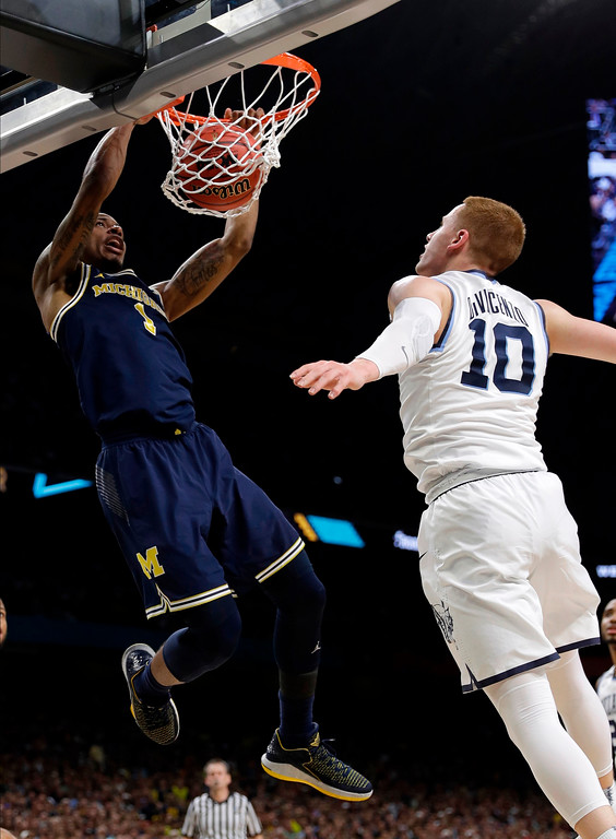 . Michigan guard Charles Matthews, left, dunks the ball over Villanova guard Donte DiVincenzo during the first half in the championship game of the Final Four NCAA college basketball tournament, Monday, April 2, 2018, in San Antonio. (AP Photo/David J. Phillip)