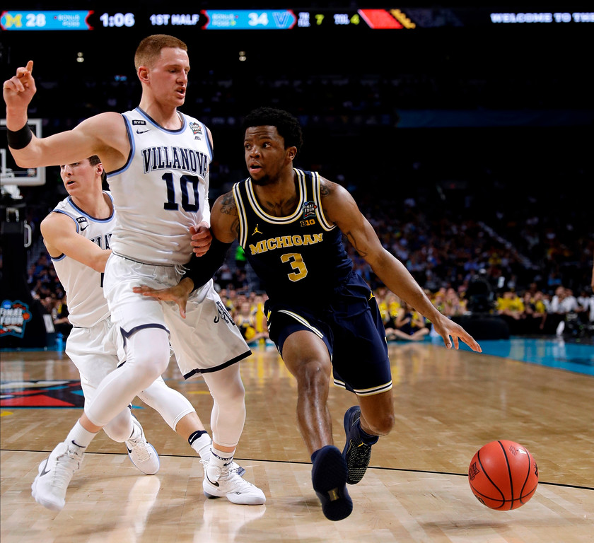 . Michigan guard Zavier Simpson drives past Villanova guard Donte DiVincenzo, left, during the first half in the championship game of the Final Four NCAA college basketball tournament, Monday, April 2, 2018, in San Antonio. (AP Photo/David J. Phillip)