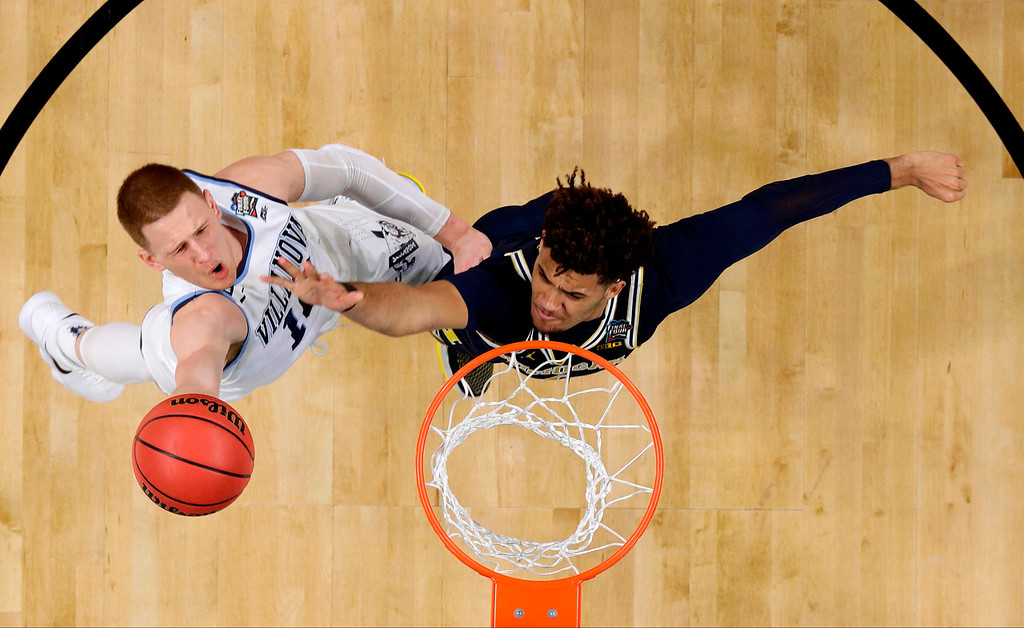 . Villanova guard Donte DiVincenzo, left, drives to the basket past Michigan forward Isaiah Livers during the first half in the championship game of the Final Four NCAA college basketball tournament, Monday, April 2, 2018, in San Antonio. (AP Photo/Eric Gay)