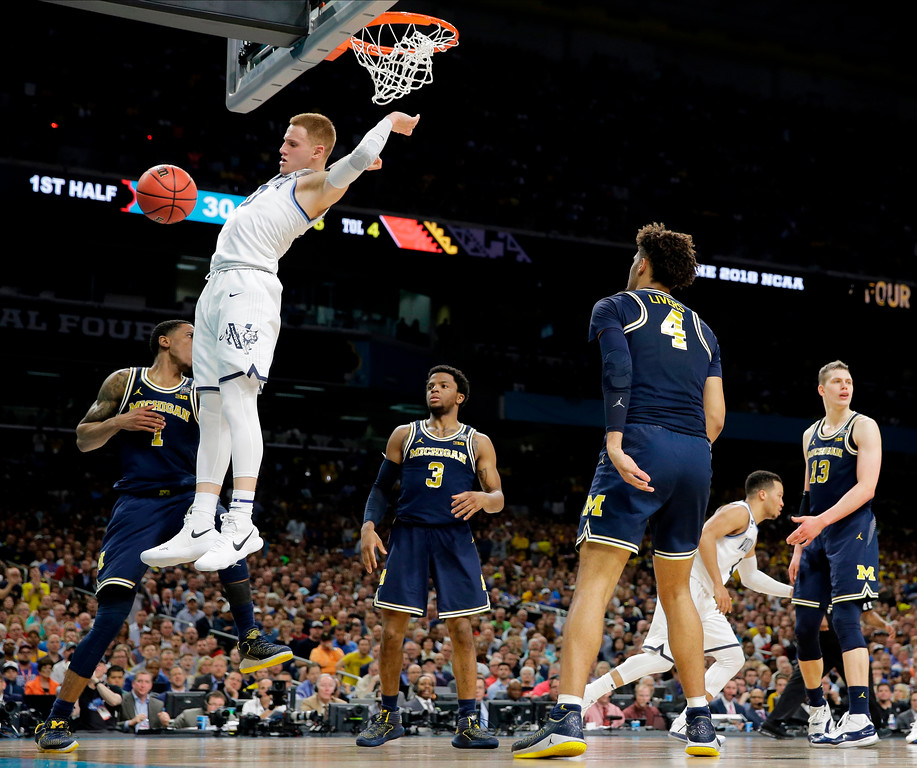 . Villanova guard Donte DiVincenzo dunks the ball over Michigan guard Charles Matthews, left, during the first half in the championship game of the Final Four NCAA college basketball tournament, Monday, April 2, 2018, in San Antonio. (AP Photo/Eric Gay)