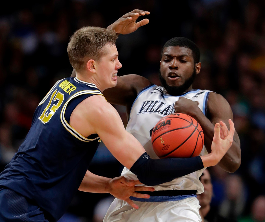 . Michigan forward Moritz Wagner, left, fights for a loose ball with Villanova forward Eric Paschall during the first half in the championship game of the Final Four NCAA college basketball tournament, Monday, April 2, 2018, in San Antonio. (AP Photo/Eric Gay)