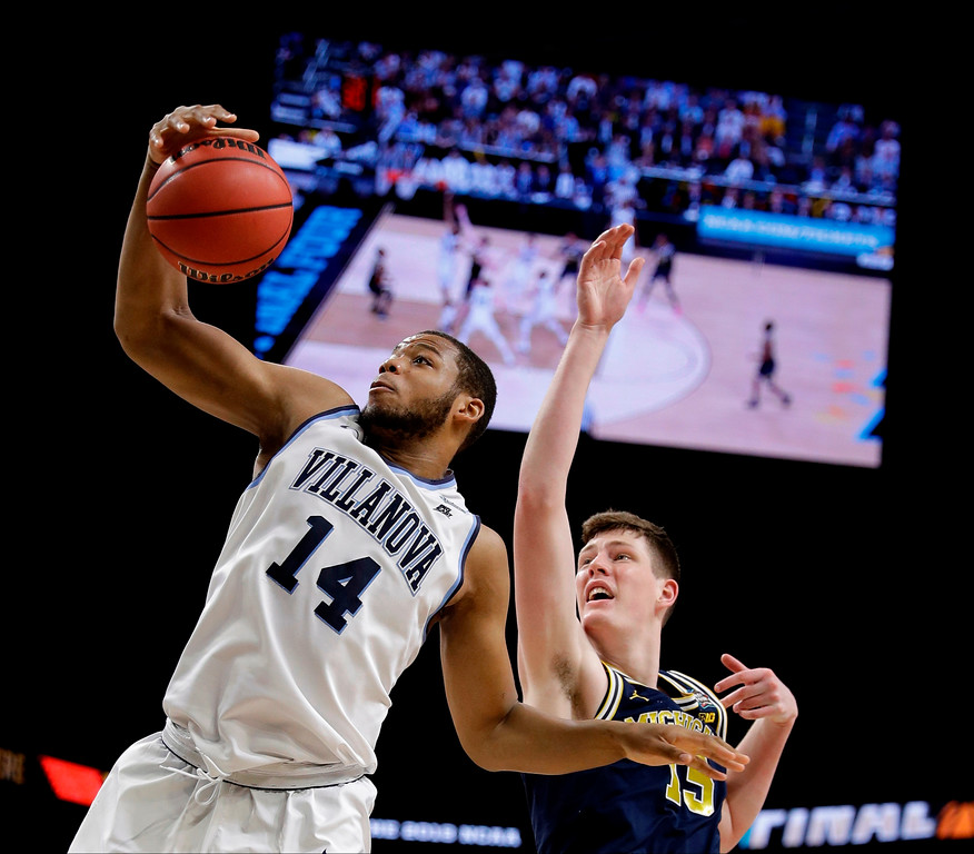 . Villanova forward Omari Spellman grabs a rebound in front of Michigan center Jon Teske, right, during the first half in the championship game of the Final Four NCAA college basketball tournament, Monday, April 2, 2018, in San Antonio. (AP Photo/David J. Phillip)