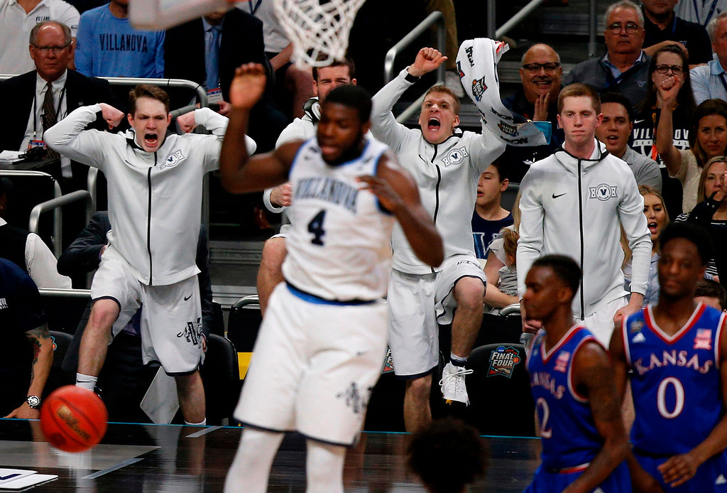 . Villanova players on the bench react as Eric Paschall (4) dunks against Kansas during the second half in the semifinals of the Final Four NCAA college basketball tournament, Saturday, March 31, 2018, in San Antonio. (AP Photo/Brynn Anderson)
