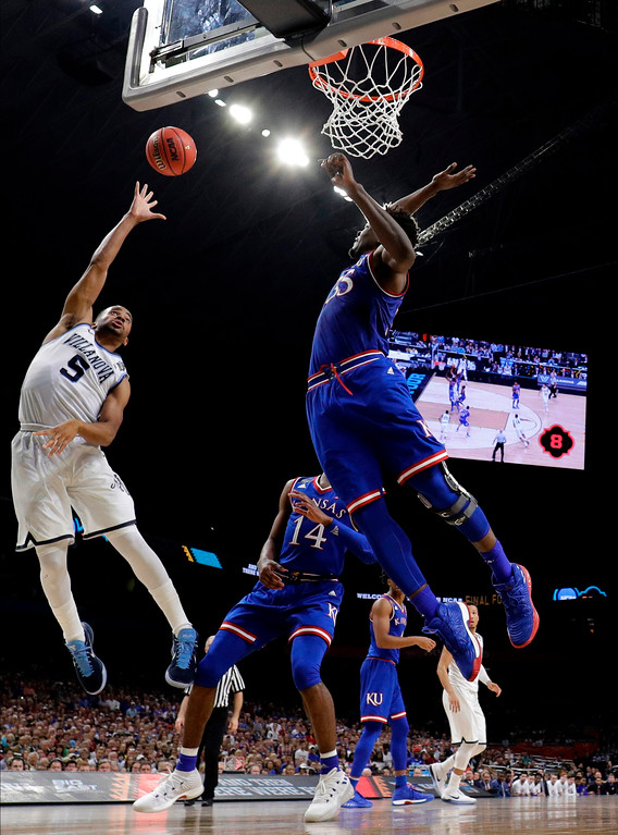 . Villanova guard Phil Booth (5) shoots over Kansas center Udoka Azubuike, right, during the second half in the semifinals of the Final Four NCAA college basketball tournament, Saturday, March 31, 2018, in San Antonio. (AP Photo/David J. Phillip)
