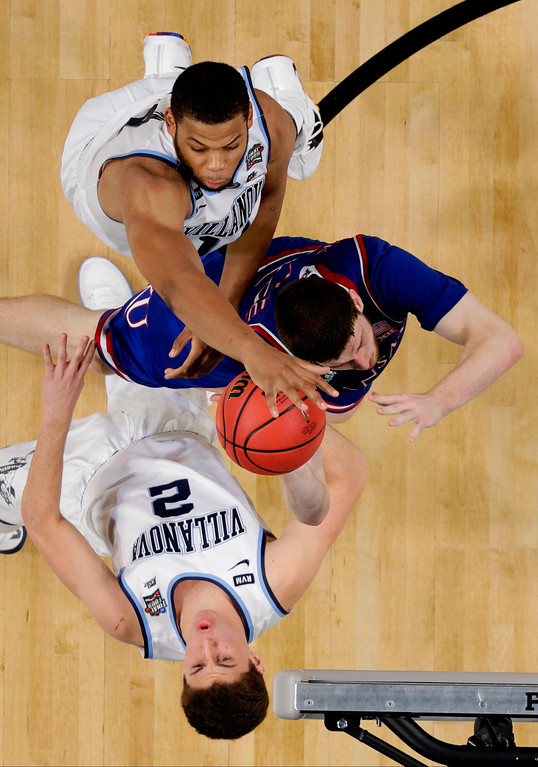 . Kansas guard Sviatoslav Mykhailiuk, center, drives to the basket between Villanova\'s Omari Spellman, top, and Collin Gillespie (2) during the second half in the semifinals of the Final Four NCAA college basketball tournament, Saturday, March 31, 2018, in San Antonio. (AP Photo/Eric Gay)