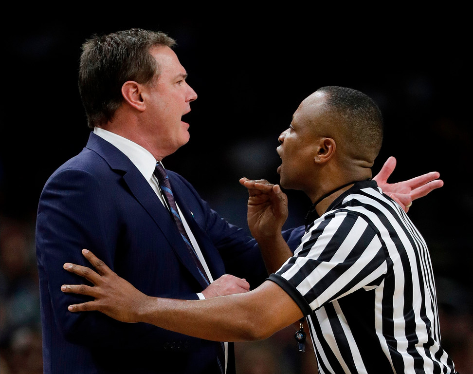 . Kansas head coach Bill Self, left, argues a call with an official during the second half in the semifinals of the Final Four NCAA college basketball tournament against Villanova, Saturday, March 31, 2018, in San Antonio. (AP Photo/David J. Phillip)