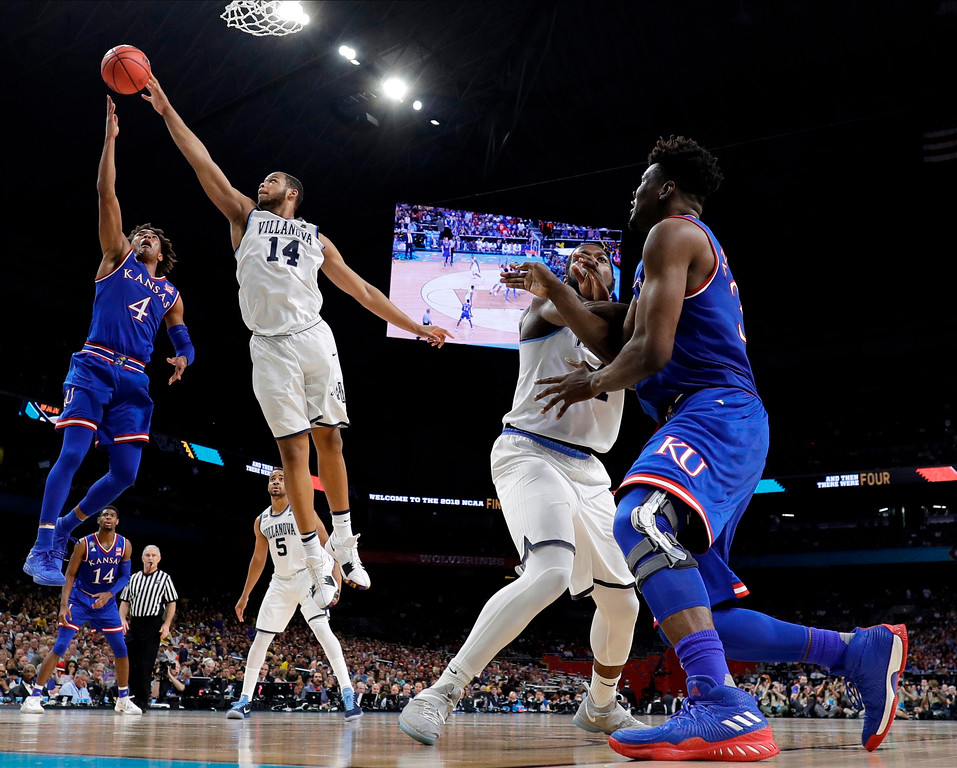 . Kansas\'s Devonte\' Graham (4) goes up for a sot against Villanova\'s Omari Spellman (14) during the second half in the semifinals of the Final Four NCAA college basketball tournament, Saturday, March 31, 2018, in San Antonio. (AP Photo/Eric Gay)