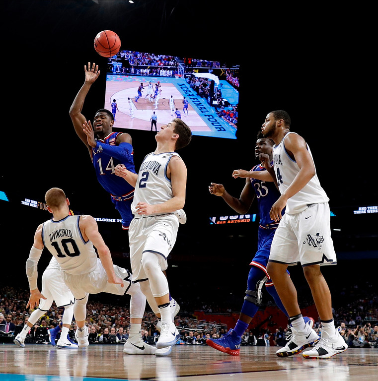 . Kansas guard Malik Newman (14) drives to the basket over Villanova\'s Donte DiVincenzo (10) and Collin Gillespie (2) during the second half in the semifinals of the Final Four NCAA college basketball tournament, Saturday, March 31, 2018, in San Antonio. (AP Photo/Eric Gay)