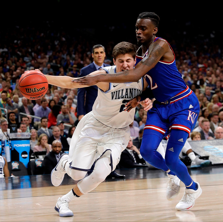 . Villanova guard Collin Gillespie, left, drives past Kansas guard Lagerald Vick during the second half in the semifinals of the Final Four NCAA college basketball tournament, Saturday, March 31, 2018, in San Antonio. (AP Photo/David J. Phillip)
