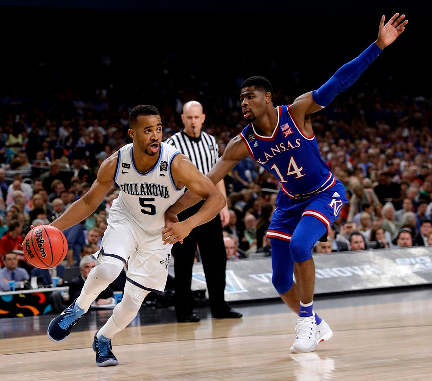 . Villanova guard Phil Booth, left, drives past Kansas guard Malik Newman during the second half in the semifinals of the Final Four NCAA college basketball tournament, Saturday, March 31, 2018, in San Antonio. (AP Photo/David J. Phillip)