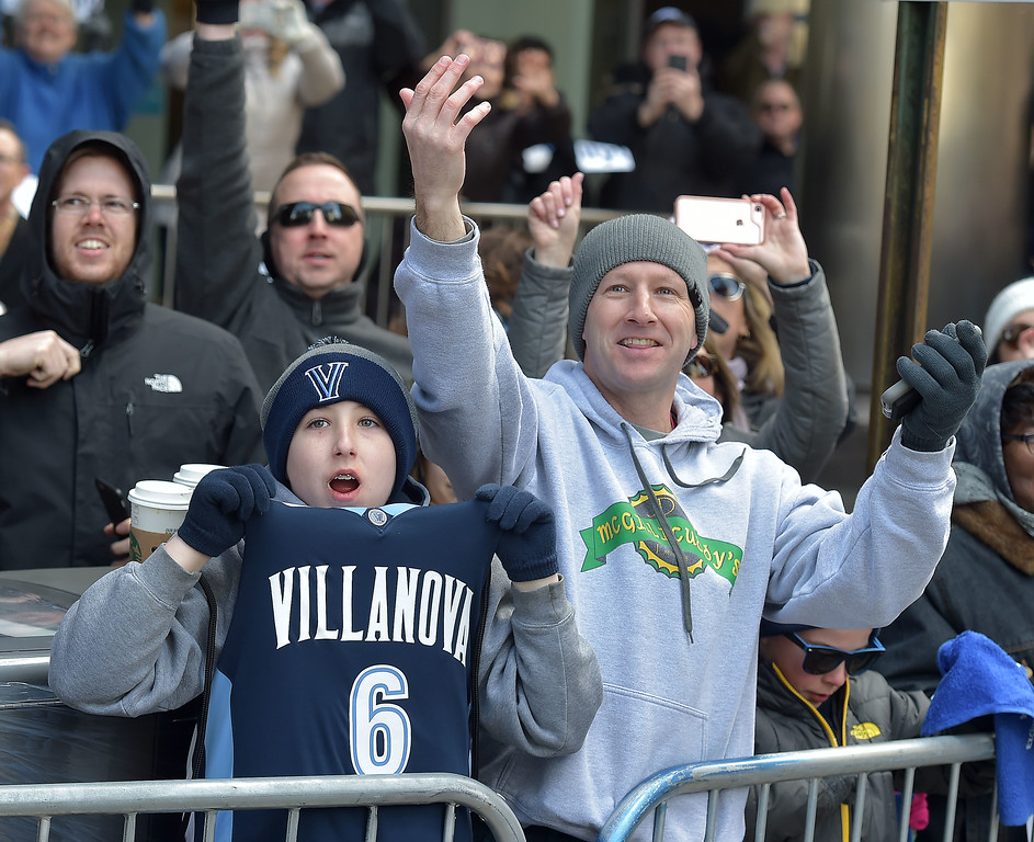 . PETE  BANNAN-DIGITAL FIRST MEDIA       Kevin Magee and his son Kevin Jr. cheer on  the Villanova Wildcat basketball team as they parade down Market St.  in celebration of the National Championship Thursday.