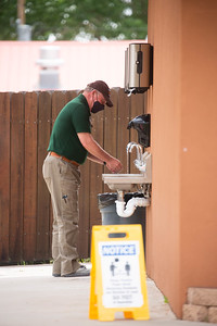 Staff member washes hands prior to entering the mess hall for lunch on May 28th, 2021.
