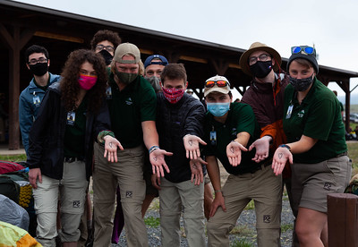 """Members of the """"Left Handed Heart Club"""" show their palms for a photo as they prepare to depart for the backcountry of Philmont on May 30, 2021. Jake Bennett (second from left in front row) is the creator of the club and said to join you have to """"do the secret handshake as awardly as possible."""""""