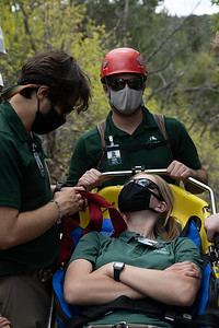 """Rangers speak with the """"patient"""" to make sure she is comfortable and has what she needs for the trip back down Lovers Leap Trail at Philmont Scout Ranch during a search and rescue training on May 26, 2021."""