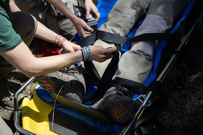"""Rangers tighten straps on the """"patient"""" for a search and rescue proceedure training on Lovers Leap Trail at Philmont Scout Ranch on May 26, 2021."""