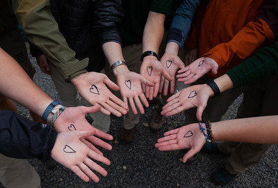"""Members of the """"Left Handed Heart Club"""" show their palms for a photo as they prepare to depart for the backcountry of Philmont on May 30, 2021. Jake Bennett, the creator of the club, said to join you have to """"do the secret handshake as awardly as possible."""""""