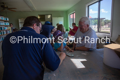 A father and grandfather help a girl paint a flower at the Philmont Training Center craft center at Philmont Scout Ranch in Cimarron, New Mexico on Monday, July 29. 2019.