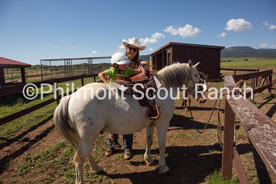 Jackie Christianson helps Teddy Pracht saddle into a unicorn pony at the Philmont Training Center pony stable at Philmont Scout Ranch in Cimarron, New Mexico on Monday, July 29. 2019.